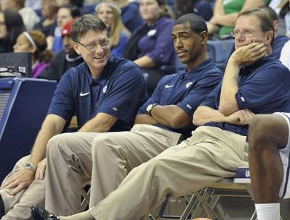Connecticut associate head coach George Blaney, right, watches First Night NCAA college basketball exhibition activities with new assistant coach Kevin Ollie, center, and new director of basketball administration Glen Miller, left, in Storrs, Conn., Friday, Oct. 15, 2010. (AP Photo/Jessica Hill)
