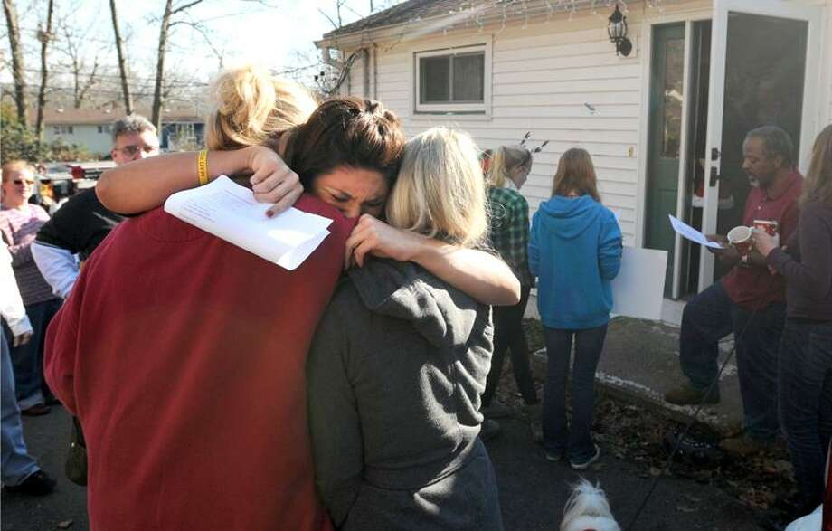 A surprised Ashley Pfeiffer, center, doles out the hugs Friday as more than 40 neighbors, friends and representatives of the Branford Fire and Police departments give her a Christmas-style sendoff in front of her Branford home. Pfeiffer is set to leave for Navy basic training. Peter Hvizdak/Register