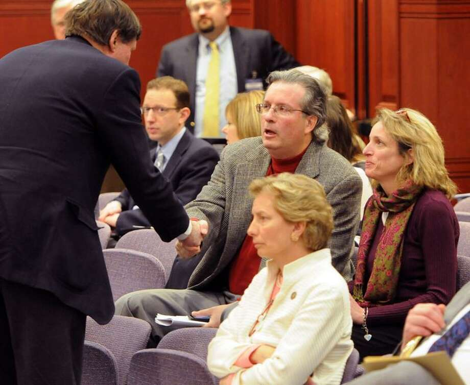 State Sen. Ed Meyer greets Dr. William Petit Jr., and his sister Johanna Petit Chapman, right, as Petit waits to testify to the Judiciary Committee Monday. Photo by Peter Hvizdak / New Haven Register