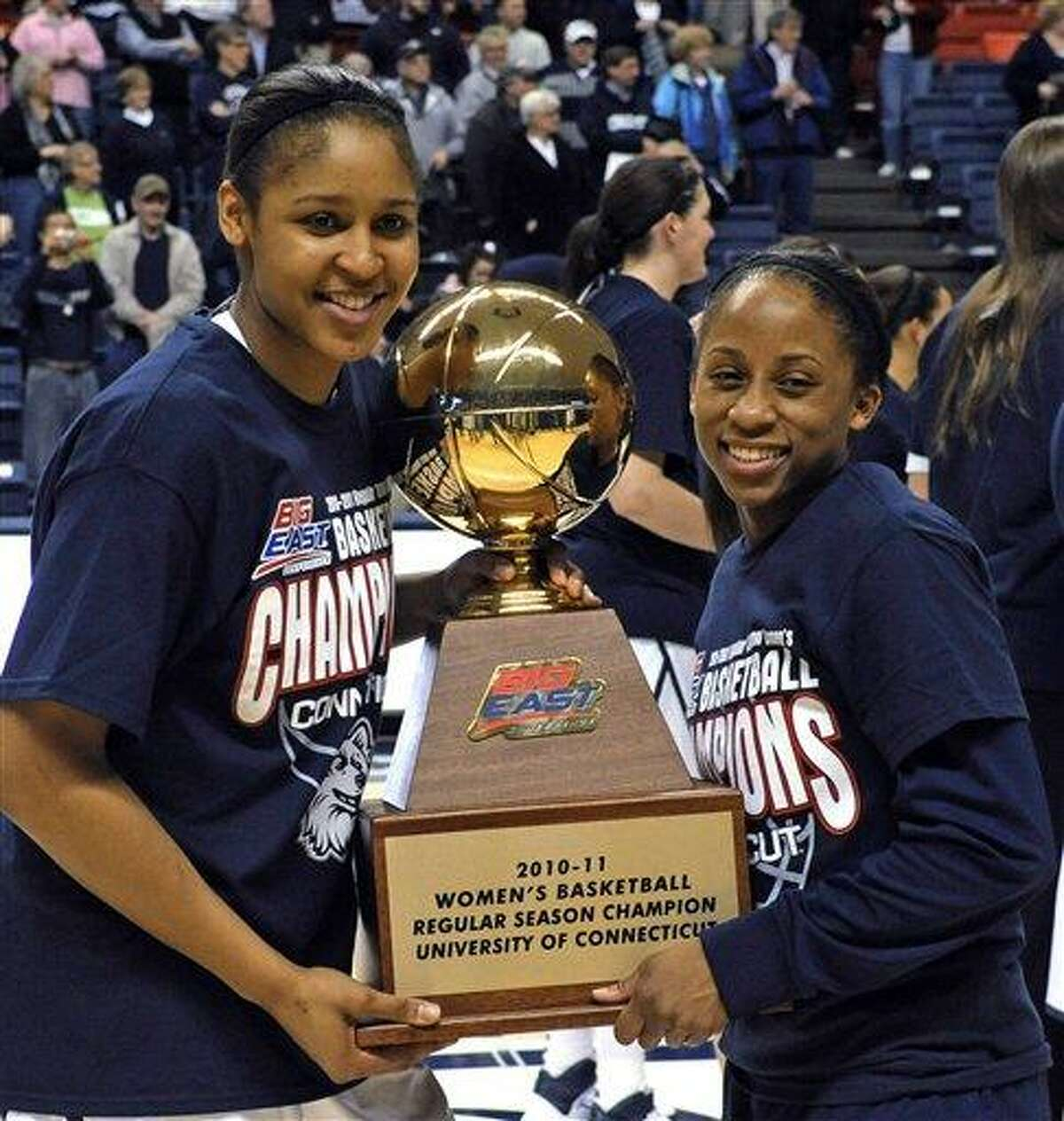 Connecticut's Maya Moore, left, and Lorin Dixon hold the Big East regular-season championship trophy after Connecticut defeated Syracuse 82-47 in an NCAA college basketball game Monday, Feb. 28, 2011, in Storrs, Conn. (AP Photo/Bob Child)