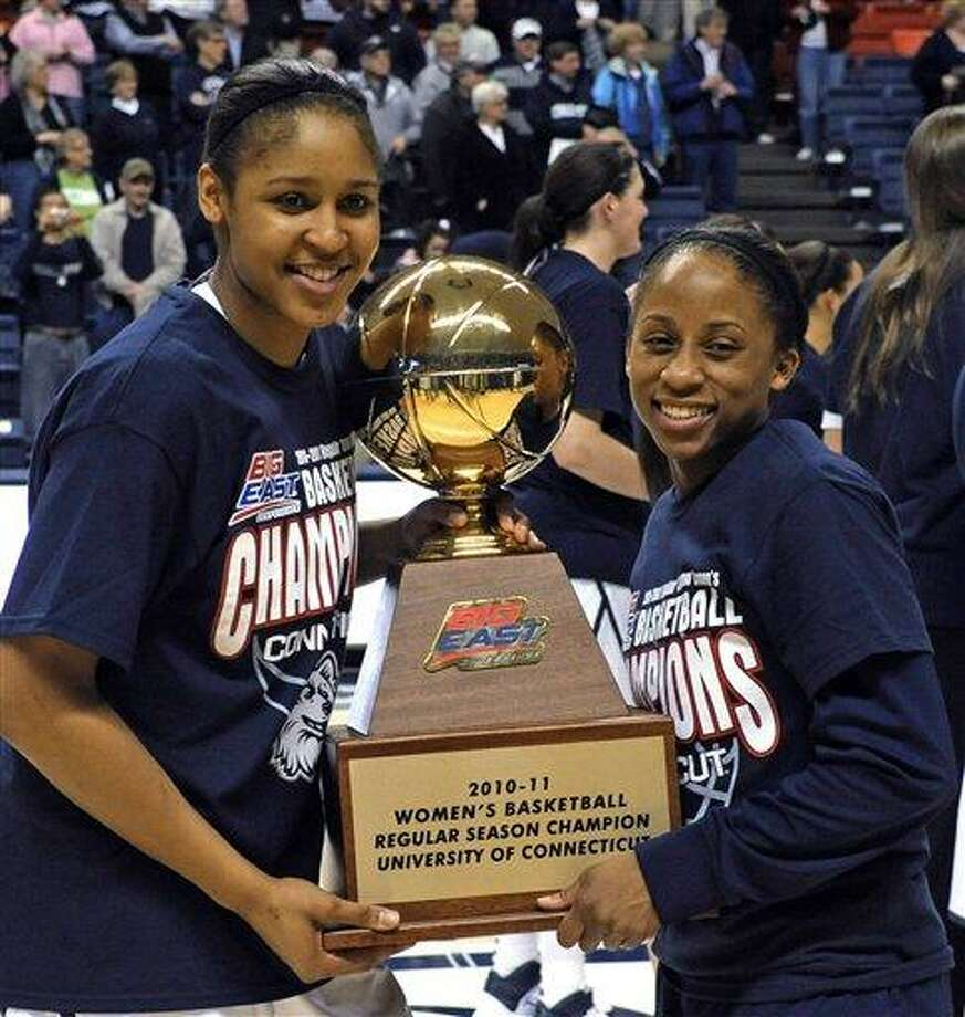 Connecticut's Maya Moore, left, and Lorin Dixon hold the Big East regular-season championship trophy after Connecticut defeated Syracuse 82-47 in an NCAA college basketball game Monday, Feb. 28, 2011, in Storrs, Conn. (AP Photo/Bob Child) Photo: AP / FRE 170410 AP