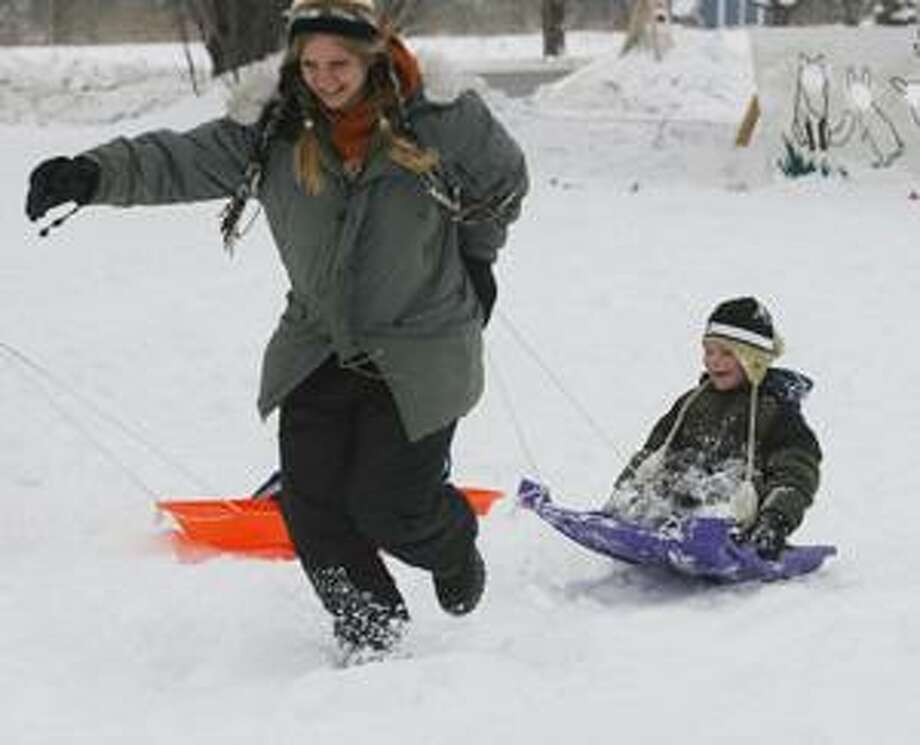 Photo by JOHN HAEGER Eli Albro, 5, holds onto the sled as he is pulled by his mother Tiffany White during a sled race at the Great Swamp's annual Winter Hibernation Festival on Saturday, Feb. 26, 2011. Albro and White are from Sherrill.