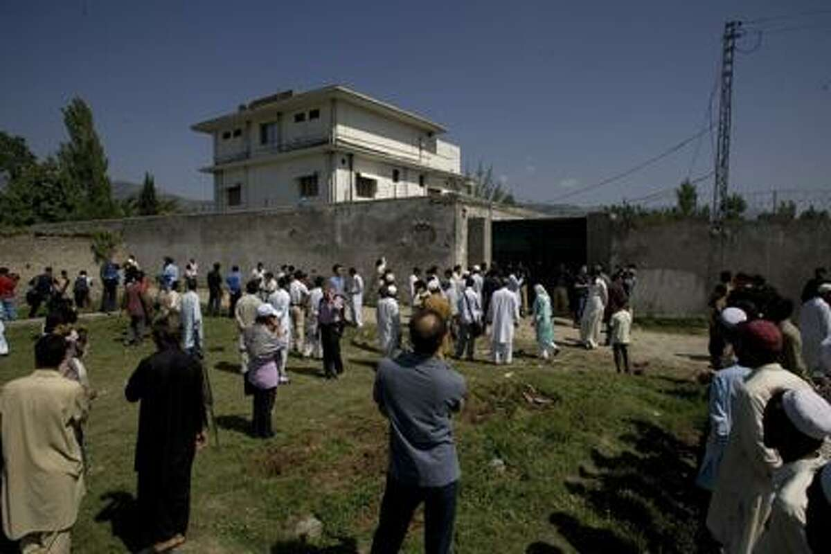 AP Photo Local people and media gather outside the perimeter wall and sealed gate into the compound and a house where al-Qaida leader Osama bin Laden was caught and killed late Monday, in Abbottabad, Pakistan, on Tuesday, May 3, 2011. Local residents showed off small parts of what appeared to be a U.S. helicopter that Washington said malfunctioned and was disabled by the American commando strike team as they retreated, while Pakistan's leader on Tuesday denied suggestions that his country's security forces had sheltered Osama bin Laden.