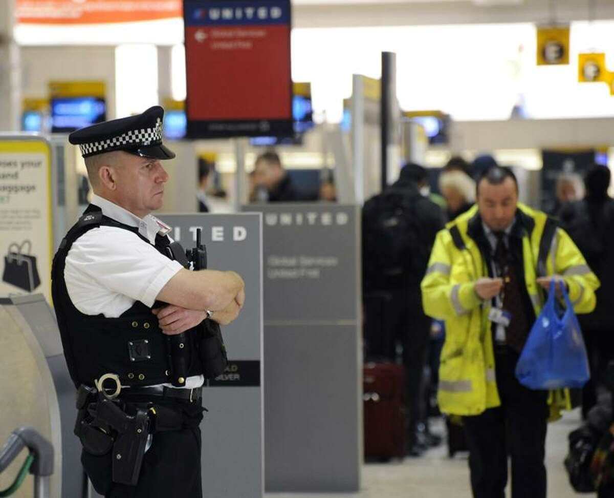 An armed police officer stands guard at Heathrow Airport in London. After the 9/11 attacks, air travel changed from a routine exercise into a process of seemingly ever-changing rules and procedures. (Associated Press file photo)