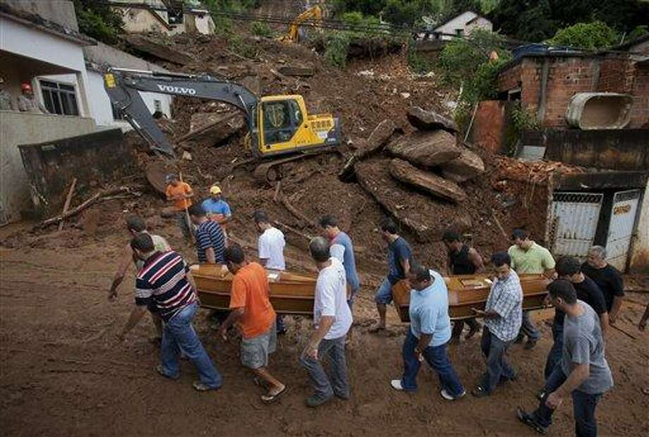 Relatives carry the coffins of a family killed by a mudslide to the cemetery in Jamapara, Rio de Janeiro state, Brazil, Tuesday Jan. 10, 2012. Sergio Carvalho, his wife Solange and their son Tiago were buried by a mudslide that killed at least eight people and left 20 people missing.  According to civil defense officials, at least 23 people have died this year due to mudslides triggered by heavy rains.  (AP Photo/Victor R. Caivano) Photo: AP / AP