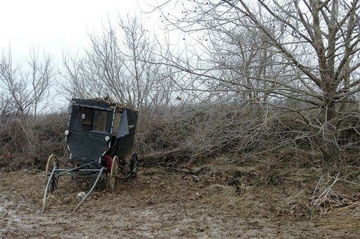 The buggy of an Amish family that was caught in a flash flood is seen in a field along Roscoe Creek, Friday, Feb. 25, 2011, in Hickman County near Dublin, Ky. Four children died late Thursday as the family sought to ford a rain-swollen creek in the horse-drawn buggy. (AP Photo/The Paducah Sun, Stephen Lance Dennee)