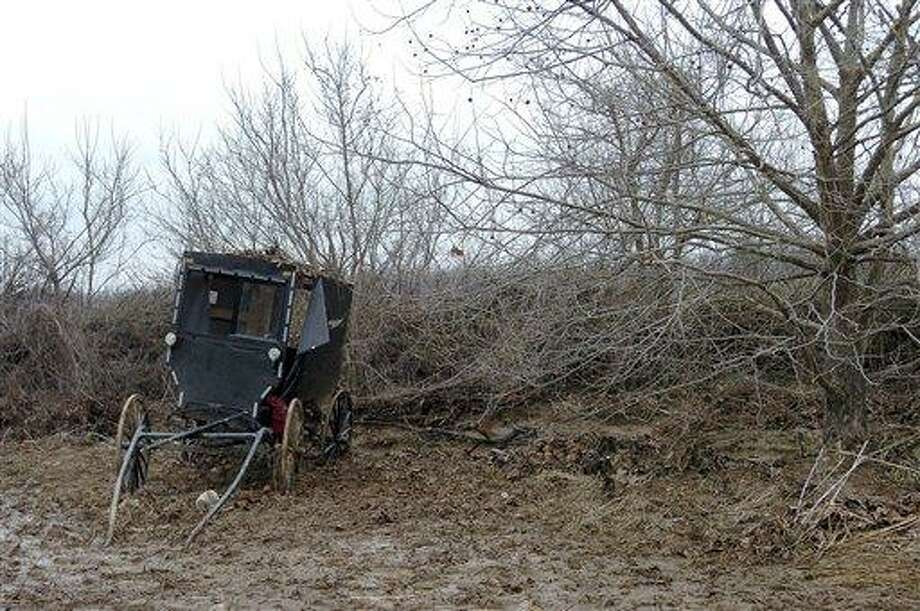 The buggy of an Amish family that was caught in a flash flood is seen in a field along Roscoe Creek, Friday, Feb. 25, 2011, in Hickman County near Dublin, Ky. Four children died late Thursday as the family sought to ford a rain-swollen creek in the horse-drawn buggy. (AP Photo/The Paducah Sun, Stephen Lance Dennee) Photo: AP / The Paducah Sun