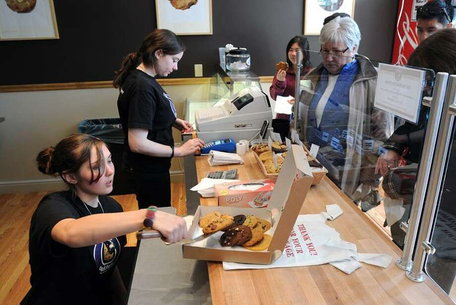 Insomnia Cookies workers Jessica Bachinski, front, and Una Casey serve up cookies to a busy crowd following the grand opening celebration of the new Chapel Street eatery.    Peter Casolino/Register