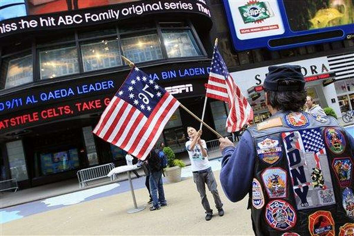 Jose Colon, right, of Manhattan, and Colin Marshal, of Little Falls, N.J. wave American flags in New York's Times Square on Monday, May 2, 2011. The Obama administration used DNA testing and other means to confirm that elite American forces in Pakistan had in fact killed Osama bin Laden, the mastermind behind the Sept. 11, 2001 terrorist attacks, officials said Monday. (AP Photo/Mary Altaffer)