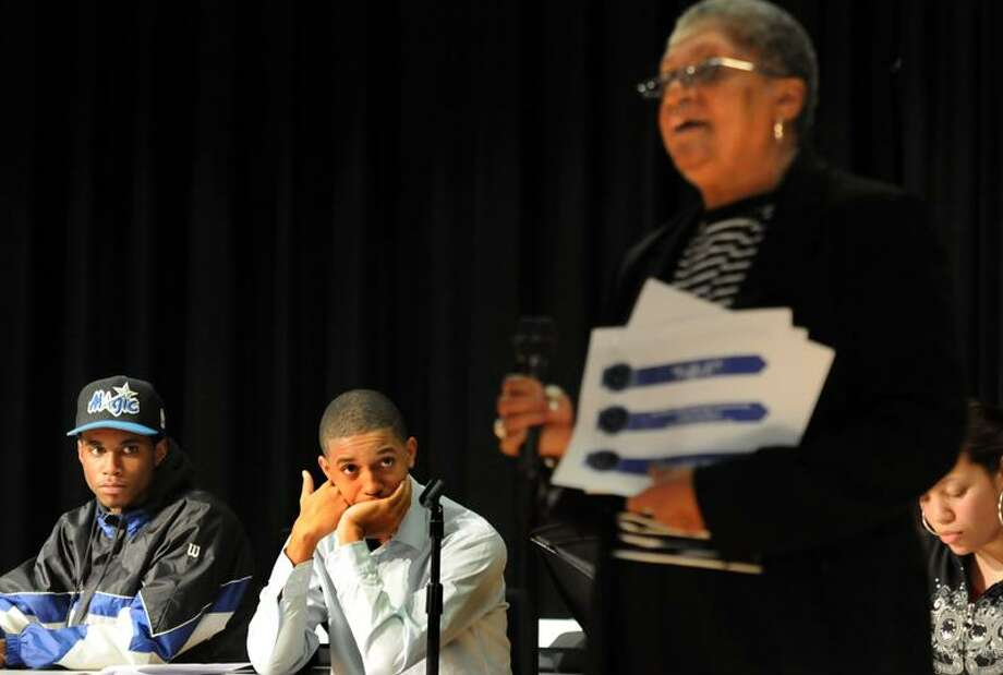 New Haven's Wexler-Grant School was the site for a youth-led forum to hear from the community about reopening the Dixwell Q House. Two of the forum organizers, Josh Williams, left, and his brother Kenneth, center, both of New Haven listen to Jacqueline Bracey of Hamden talk about the Q House. Mara Lavitt/Register