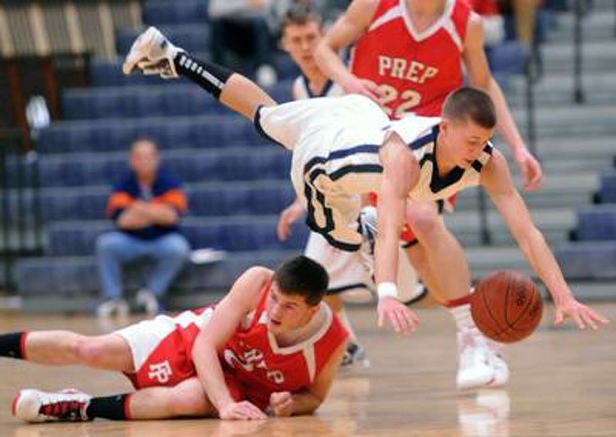 East Haven--Lyman Hall's PJ Higgins leaps over Fairfield Prep's Robbie Bier during Saturday's SCC boys' basketball quarterfinal at East Haven High School. Photo by Brad Horrigan/New Haven Register-02.26.11.