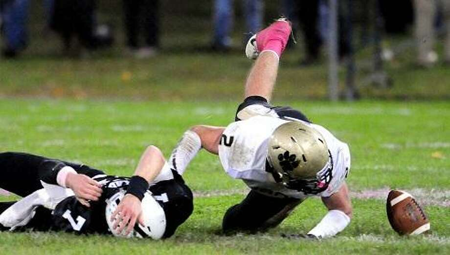 Xavier quarterback Tim Doyle (left) fumbles the ball against Daniel Hand in the first half at Palmer Field in Middletown on 10/12/2012. Peter Gerson (right) of Daniel Hand recovered the ball on the play.Photo by Arnold Gold/New Haven Register