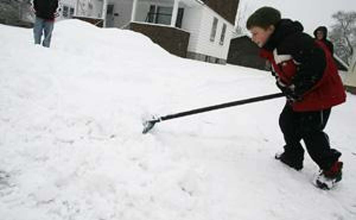 Dispatch Staff Photo by JOHN HAEGER Gabriel Williams, 8, of Sherrill shovels his driveway on Friday, Feb. 25, 2011.