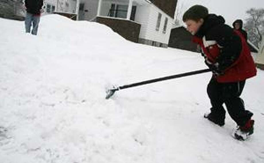 Dispatch Staff Photo by JOHN HAEGER Gabriel Williams, 8, of Sherrill shovels his driveway on Friday, Feb. 25, 2011.