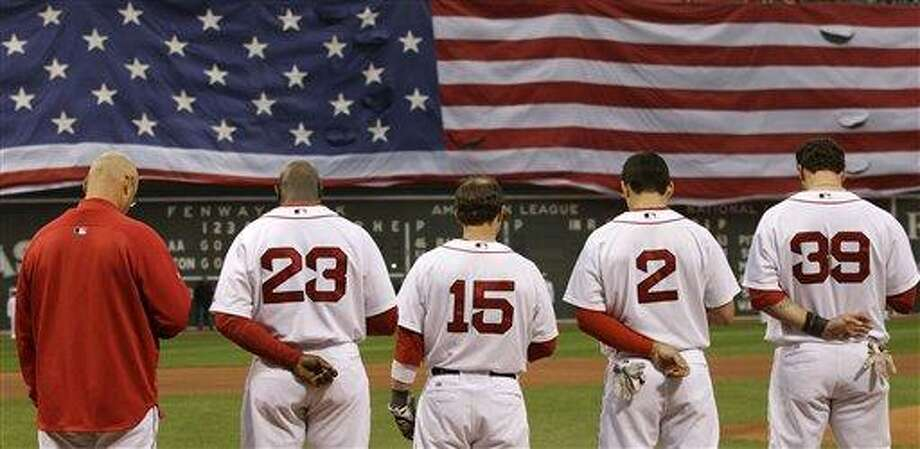 As a giant U.S. flag drops across the left field wall, Boston Red Sox pause for a moment of silence prior to facing the Los Angeles Angels in a baseball game in Boston, Monday, May 2, 2011. The Red Sox honored those who died on Sept. 11, 2001, a day after the raid on Osama bin Laden's compound in Pakistan.  From left are manager Terry Francona, Mike Cameron, Dustin Pedroia, Jacoby Ellsbury and Jarrod Saltalamacchia. (AP Photo/Charles Krupa) Photo: AP / AP