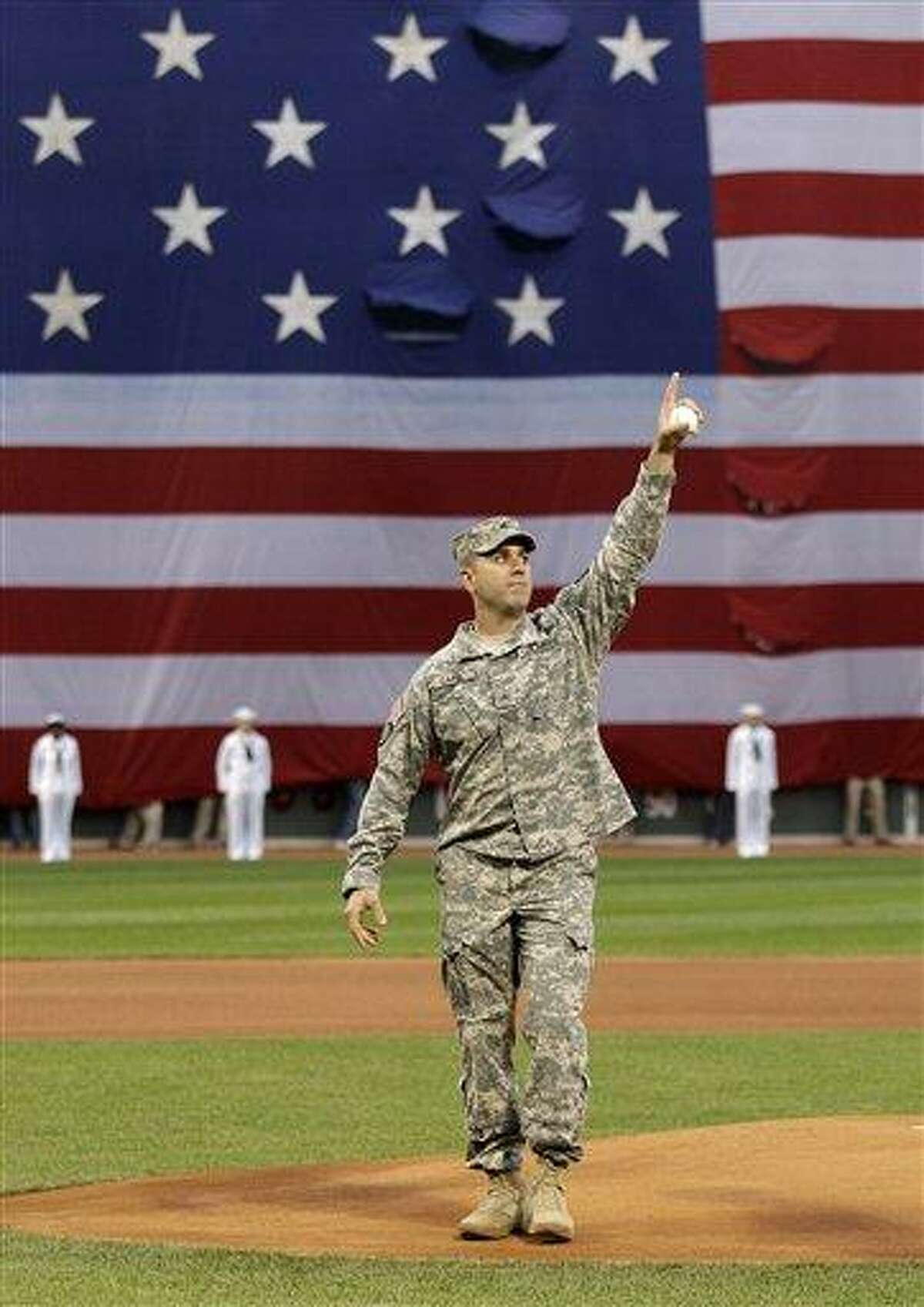 With a giant U.S. flag draped across the left field wall, U.S. Army Ranger Sgt. Lucas Carr, of the South Boston neighborhood of Boston, acknowledges fans prior to throwing out the ceremonial first pitch prior to a baseball game between the Boston Red Sox and the Los Angeles Angels at Fenway Park in Boston, Monday, May 2, 2011. The Red Sox honored those who died in the attacks of Sept. 11, 2001. (AP Photo/Charles Krupa)