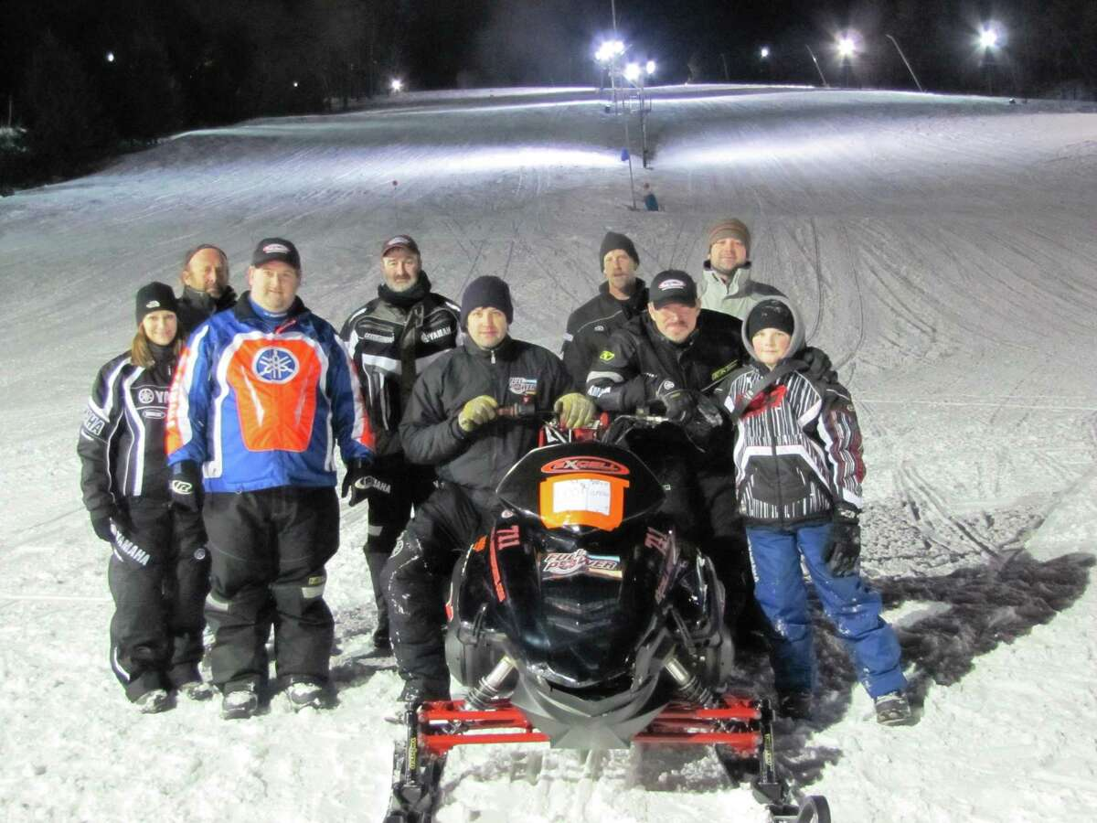"""Submitted Photo by Devin Webb Excell Motorsports, of Hubbardsville, won the title of """"King of the Hill"""" at Toggenburg Ski Center's snowmobile hill climb February 20. Aaron Excell drove the custom-built 1000cc 450HP turbo-charged Yamaha that took the crown in the 2000cc Pro modified class. Excell Motorsports and Justin Fuller, of Full Power Performance, teamed up for the competition. The turbo-charged Yamaha averages 110 mph up-hill in 660 feet. The members of the Excell team are, Justin Fuller, Aaron Excell, Austin Excell, Dan Williams, Randy Stevens, Todd Roher, Harold Reed, Ed Carhart and Tori Carhart."""