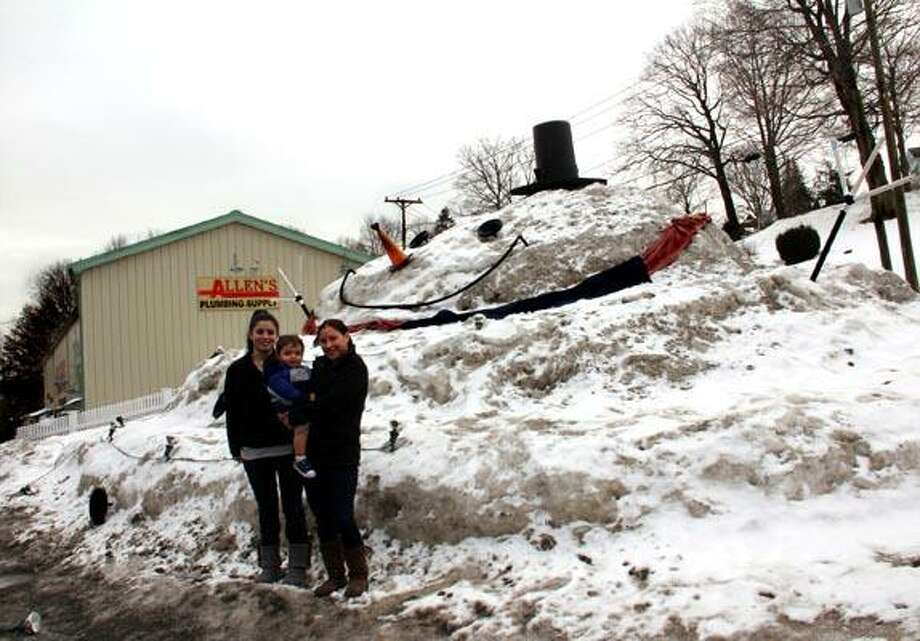 Employees of Allen's Plumbing Supply in Seymour built a massive snowman.  Christine Santora, 2 year old Griffin Gould (grandson of store owner John Allen), and Sarah Calabrese. (Photo by NeRonda Langley)