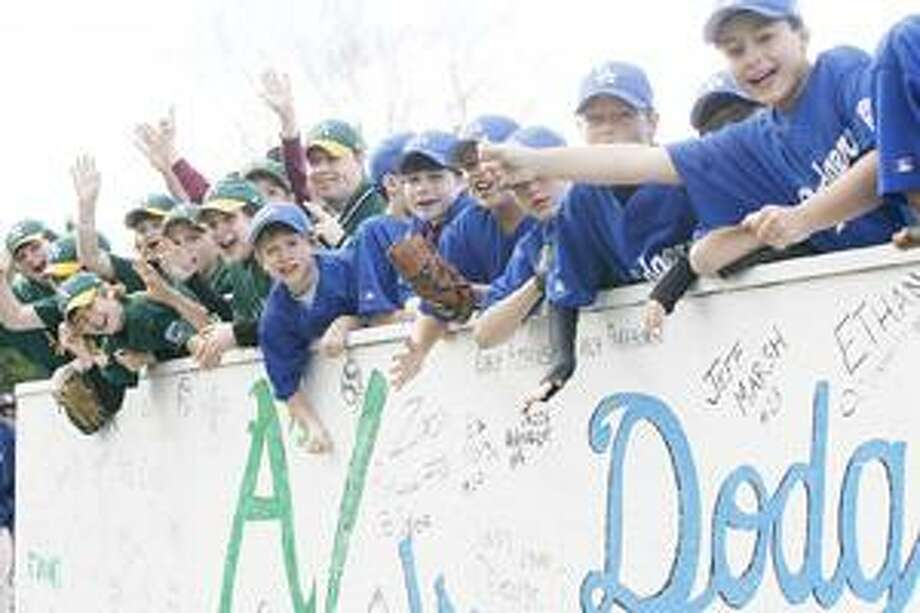 Photo by JOHN HAEGER Canastota Little League Major League members wave and cheer during the parade to open the 60th season of Little League in Canastota on Saturday, April 30, 2011.