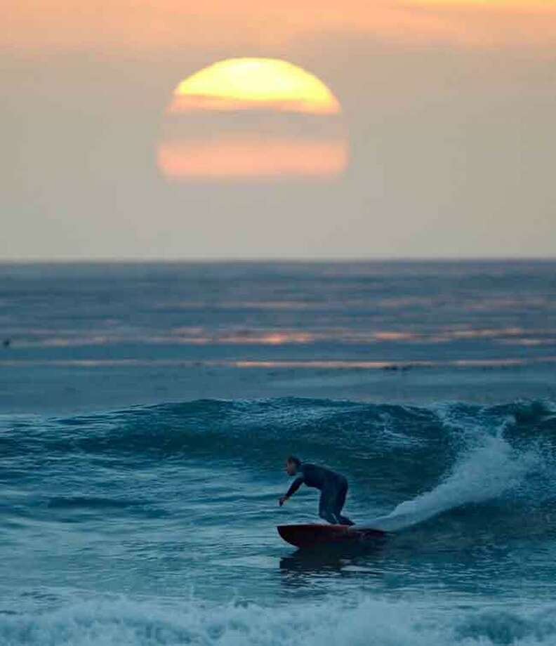 A surfer takes advantage of summer like weather and a high surf as he maneuvers through waves as the sun sets Friday, Jan. 6, in Encinitas, Calif. Associated PRess Photo: ASSOCIATED PRESS / AP2012