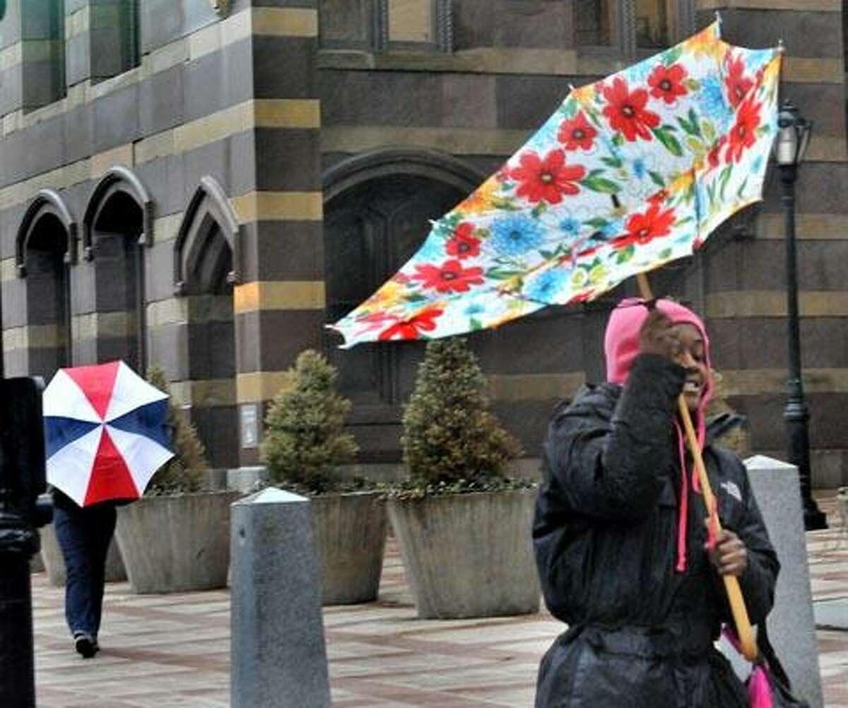 Sharnaye Butler, of Waterbury, loses control of her umberella as she walks up Church Street in New Haven on Friday. (Melanie Stengel/Register)