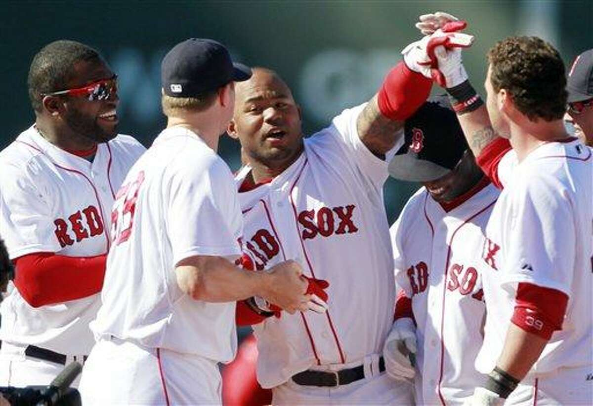 Boston Red Sox's Carl Crawford, third from left, celebrates with teammates after his RBI single scored Jed Lowrie to beat the Seattle Mariners 3-2 in the ninth inning of an MLB baseball game, Sunday, May 1, 2011, in Boston. (AP Photo/Michael Dwyer)