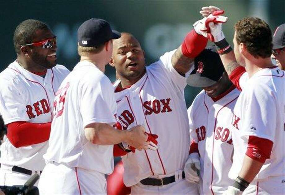 Boston Red Sox's Carl Crawford, third from left, celebrates with teammates after  his RBI single scored Jed Lowrie to beat the Seattle Mariners 3-2 in the ninth inning of an MLB baseball game, Sunday, May 1, 2011, in Boston. (AP Photo/Michael Dwyer) Photo: AP / AP