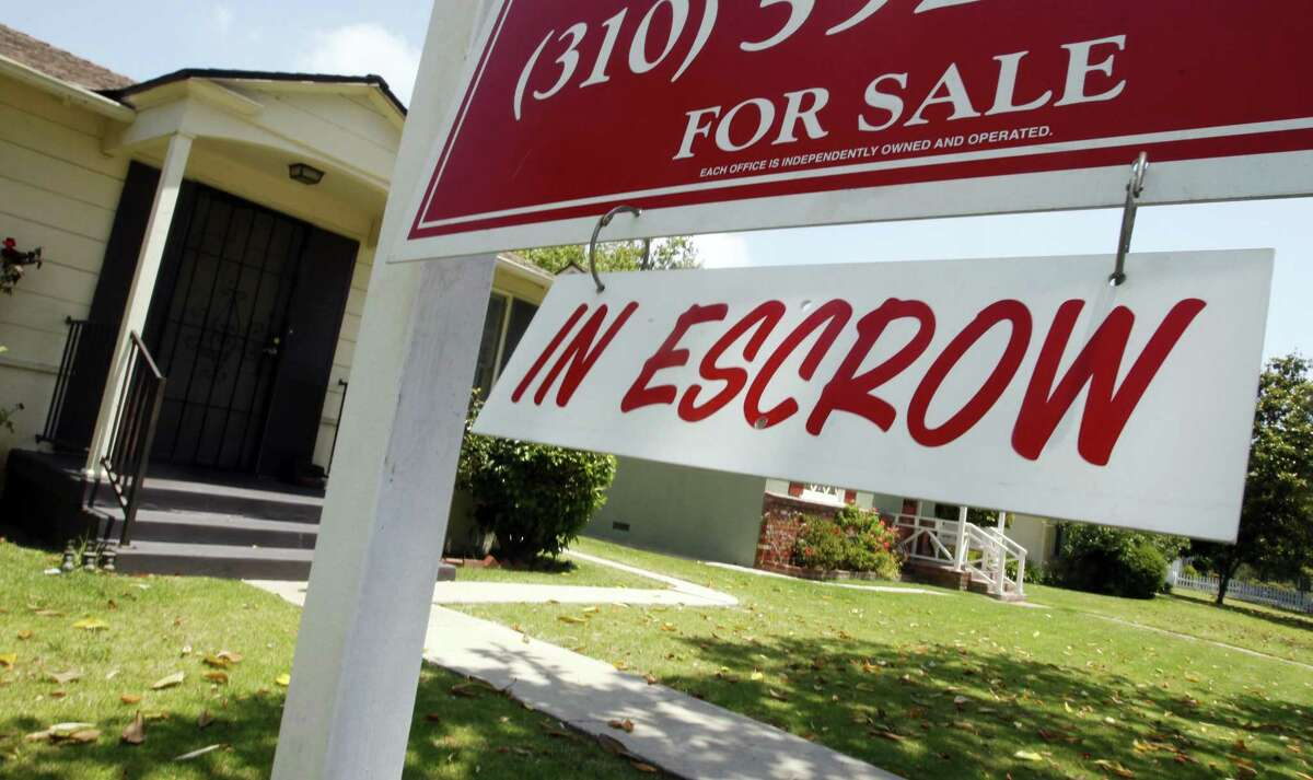 In this June 13 photo, a home is posted as 'in escrow,' displayed in Los Angeles. The number of people who signed contracts to buy homes rose sharply in May, pushed higher by an influx of spring buying. (AP Photo/Reed Saxon)