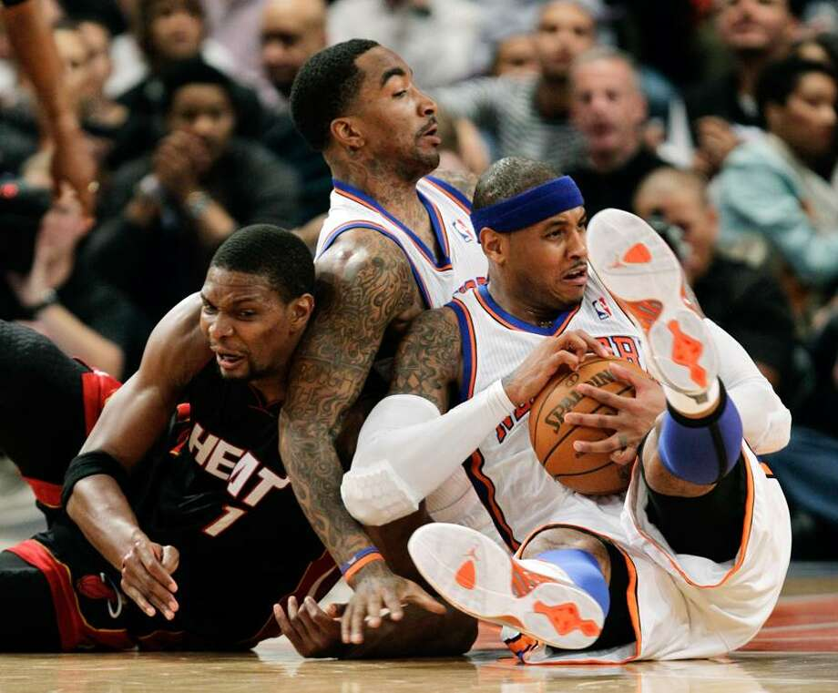 Miami Heat forward Chris Bosh (1), New York Knicks guard J.R. Smith, center, and Knicks forward Carmelo Anthony scramble for a loose ball in the first half of Game 3 of an NBA basketball first-round playoff series at Madison Square Garden in New York, Thursday, May 3, 2012. (AP Photo/Kathy Willens) Photo: AP / AP2012