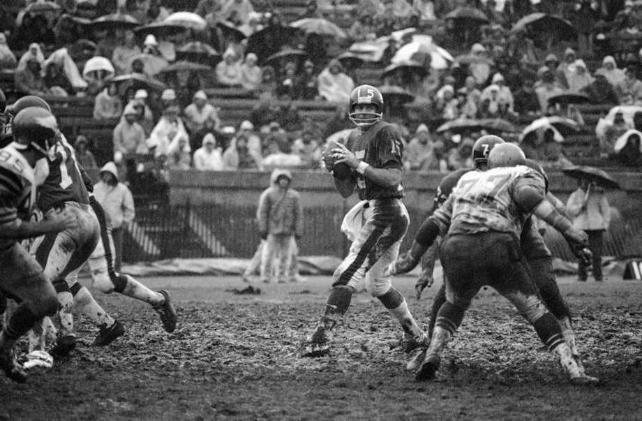 New York Giants quarterback Craig Morton looks downfield for a receiver late in the Giants Philadelphia Eagles game at Yale Bowl in New Haven, Connecticut, on Sunday, Dec. 8, 1974. Face to-face in front of Morton are Eagles Jerry Patton (77 in light jersey) and Giants Tom Mullen. Due to heavy rains, the field was a sea of mud. (AP Photo) Photo: ASSOCIATED PRESS / AP1974