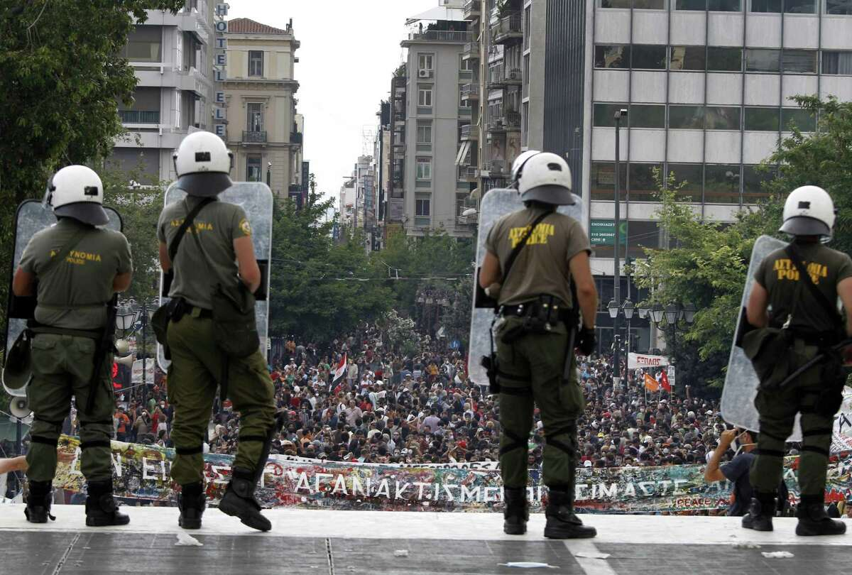 Riot police watch over protesters during a demonstration in Athens on Tuesday. Youths hurled rocks and fire bombs at riot police in central Athens on Tuesday as a general strike against new austerity measures brought the country to a standstill. (AP Photo/Petros Karadjias)