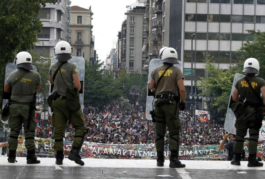 Riot police watch over protesters during a demonstration in Athens on Tuesday. Youths hurled rocks and fire bombs at riot police in central Athens on Tuesday as a general strike against new austerity measures brought the country to a standstill. (AP Photo/Petros Karadjias) Photo: AP / AP