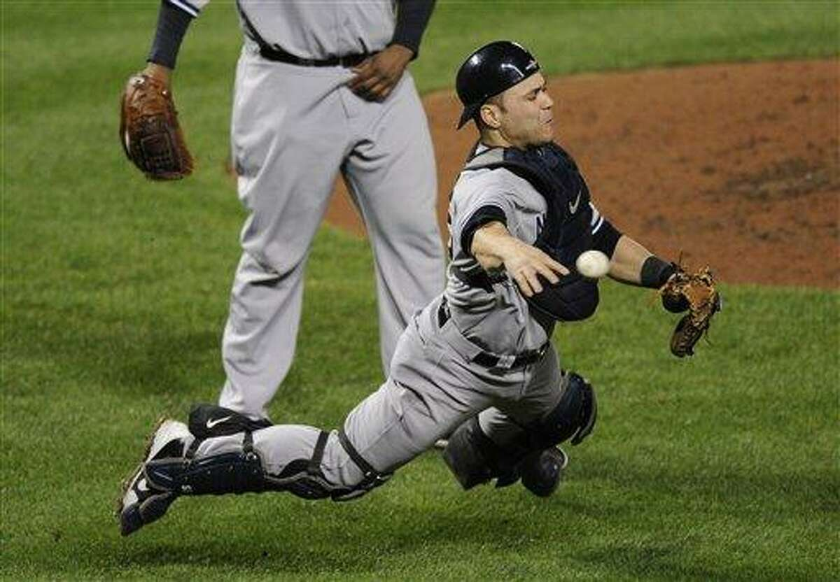New York Yankees catcher Russell Martin throws out Baltimore Orioles' Lew Ford, not pictured, at first base in the fifth inning of Game 1 of the American League division baseball series on Sunday, Oct. 7, 2012, in Baltimore. (AP Photo/Nick Wass)
