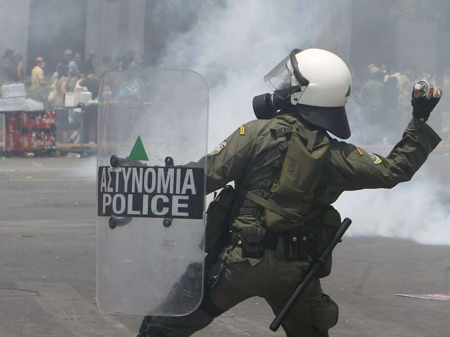 A riot police officer throws tear gas at protesters in Syntagma square in front of  Parliament Wednesday. Associated Press Photo: AP / AP