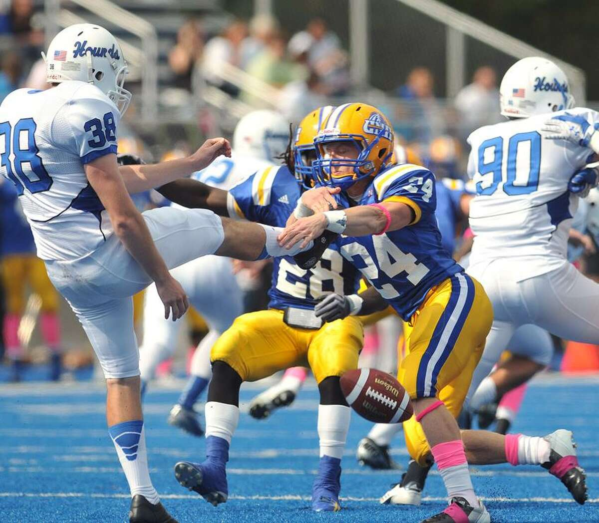 West Haven--UNH's Matt Stevco blocks the punt by Assumption's Patrick Tyler, which set up a TD in the first quarter. (UNH #28, rear, is Anthony Tillman) Photo Peter Casolino/New Haven Register 10/6/12