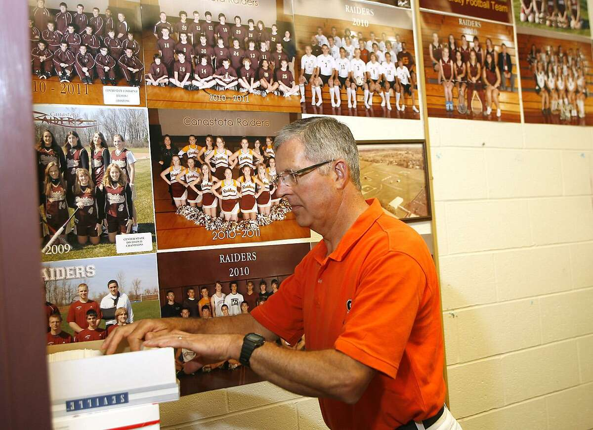 Dispatch Staff Photo by JOHN HAEGER Canastota Athletic Director Steve Tornatore sorts files in his office Tuesday, June 28, 2011. Tornatore will be retiring on July 1.