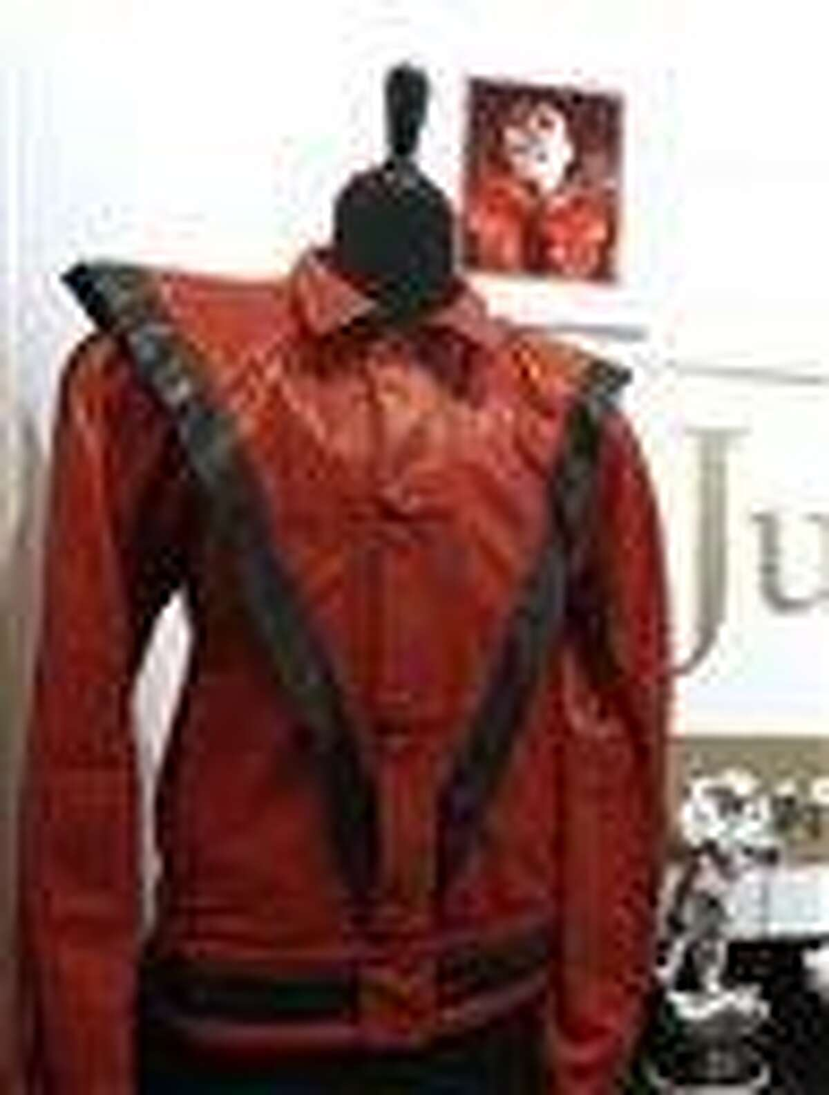"""In this photo taken May 26, 2011, a worn and signed """"Thriller"""" Jacket that belonged to Michael Jackson is shown at Julien's Auctions, in Beverly Hills, Calif. The famed black-and-red calfskin jacket that Jackson wore in the classic """"Thriller"""" video has sold for $1.8 million. Darren Julien, president and CEO of Julien's Auctions in Beverly Hills, says the jacket was purchased Sunday, June 26, 2011, by Milton Verret, a commodities trader from Austin, Texas. (AP Photo/Matt Sayles)"""