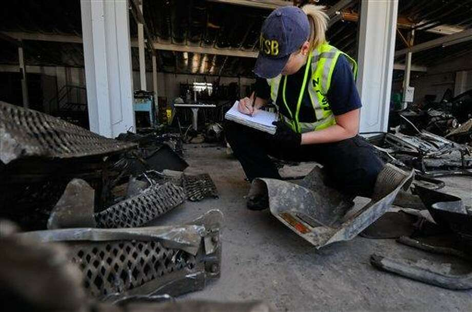 Jennifer Morrison, investigator for the National Transportation Safety Board (NTSB), works with the wreckage of the 2008 Peterbilt 367 truck-tractor at the Nevada Department of Transportation maintenance facility (NDOT) on Monday, June 27, 2011 in Fallon, Nev. The truck crashed into an Amtrak passenger car on June 24, 2011. (AP Photo/Kevin Clifford). Photo: AP / FR159396 AP