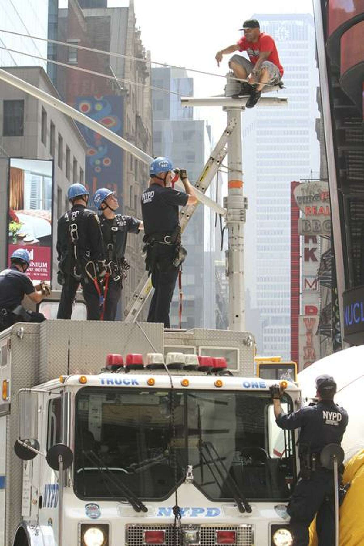 New York City police officers negotiate with an unidentified man who climbed a traffic light pole in Times Square Tuesday. Associated Press