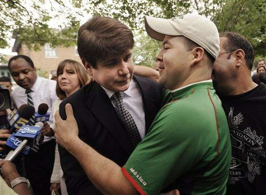 Former Illinois Gov. Rod Blagojevich left, is hugged by a supporter as he leaves his home Monday, June 27, 2011, in Chicago for the Federal court after jurors informed the judge that they had reached agreement on 18 of the 20 counts against him in his corruption retrial. A jury convicted Rod Blagojevich Monday of nearly all the corruption charges against him, including trying to sell or trade President Barack Obama's old Senate seat.(AP Photo/Paul Beaty) Photo: AP / FR36811 AP
