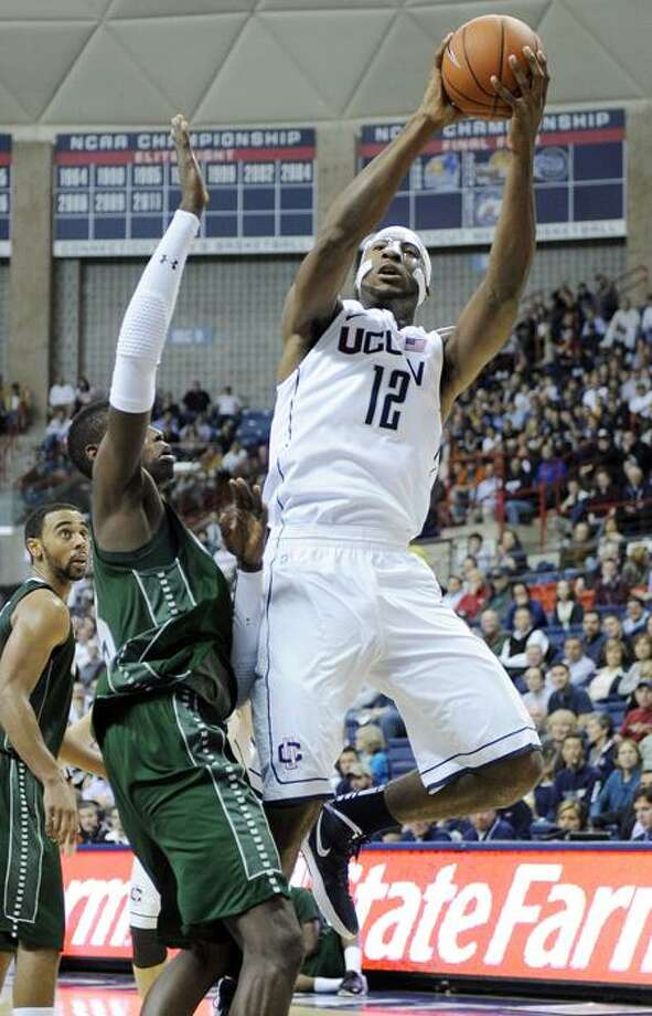 Connecticut's Andre Drummond (12) shoots over Wagner's Naofall Folahan (5) during the first half of their NCAA basketball game in Storrs, Conn., on Monday, Nov. 14, 2011. (AP Photo/Fred Beckham) Photo: AP / FR153656 AP