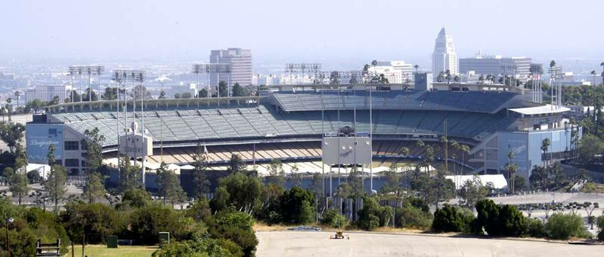 City Hall, the tall building at right, stands behind Dodger Stadium, home of baseball's Los Angeles Dodgers, in Los Angeles. On Monday, the team filed for bankruptcy protection in a Delaware court.(Associated Press)