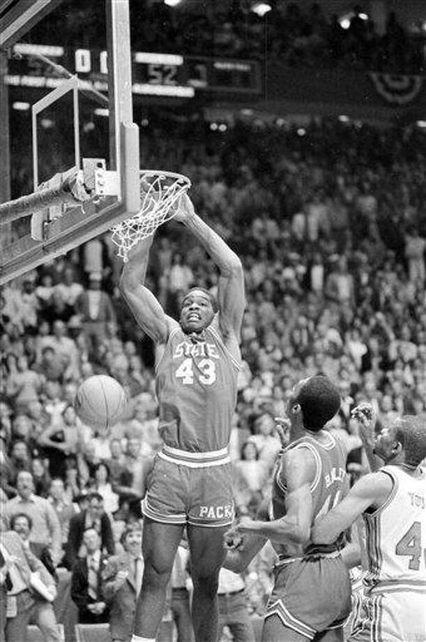 FILE- This April 4, 1983 file photo shows North Carolina State's Lorenzo Charles (43) dunking the ball in the basket to give N.C. State a 54-52 win over Houston in the NCAA Championship game in Albuquerque, N.M.  A tour bus official says the former North Carolina State basketball star , was killed when a bus he was driving crashed in Raleigh.  Charles was 47. (AP Photo/File) Photo: ASSOCIATED PRESS / AP1983