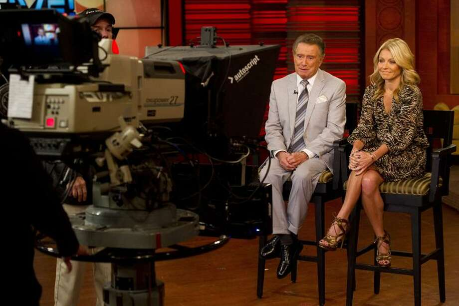 """In this Oct. 28, 2011 photo, long-time talk show host Regis Philbin appears with his co-host Kelly Ripa on set during a broadcast of """"Live! with Regis and Kelly"""", in New York.  After ruling morning television for 28 years as New York's Everyman-about-town, the co-host who made performance art of TV gab is exiting what for a decade has been known as """"Live! With Regis and Kelly."""" His last day is Nov. 18. (AP Photo/Charles Sykes) Photo: AP / AP2011"""
