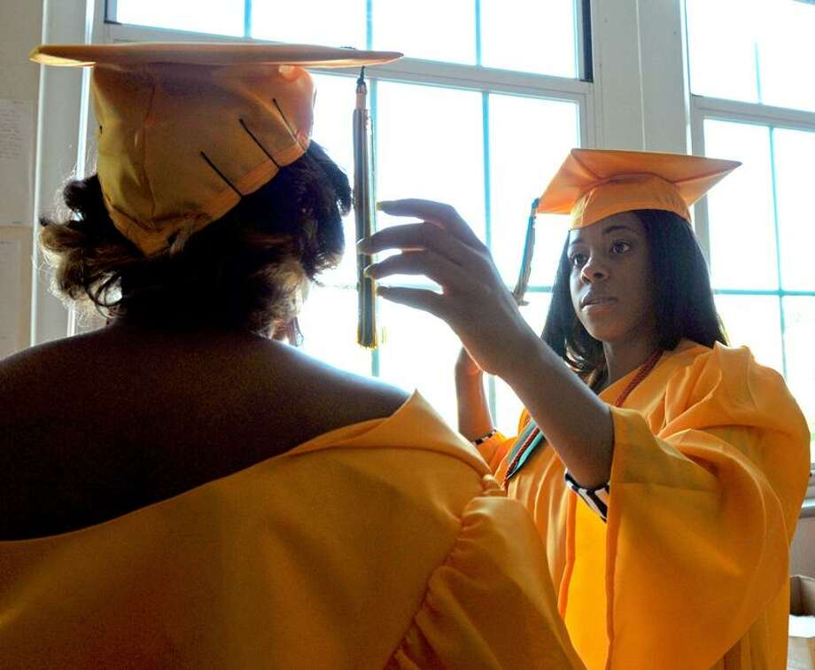 Ashley Smart, left, makes sure the hair pins are attached firmly to the mortarboard of classmate Karlene Stuckey before the start of commencement exercises Monday evening at Hamden High School.  Peter Hvizdak/Register