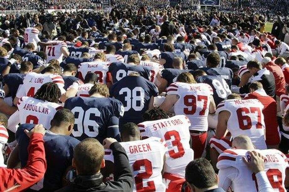 Penn State and Nebraska players gather at mid-field for a pre-game prayer before an NCAA college football game in State College, Pa., Saturday, Nov. 12, 2011. (AP Photo/Gene J. Puskar) Photo: AP / AP