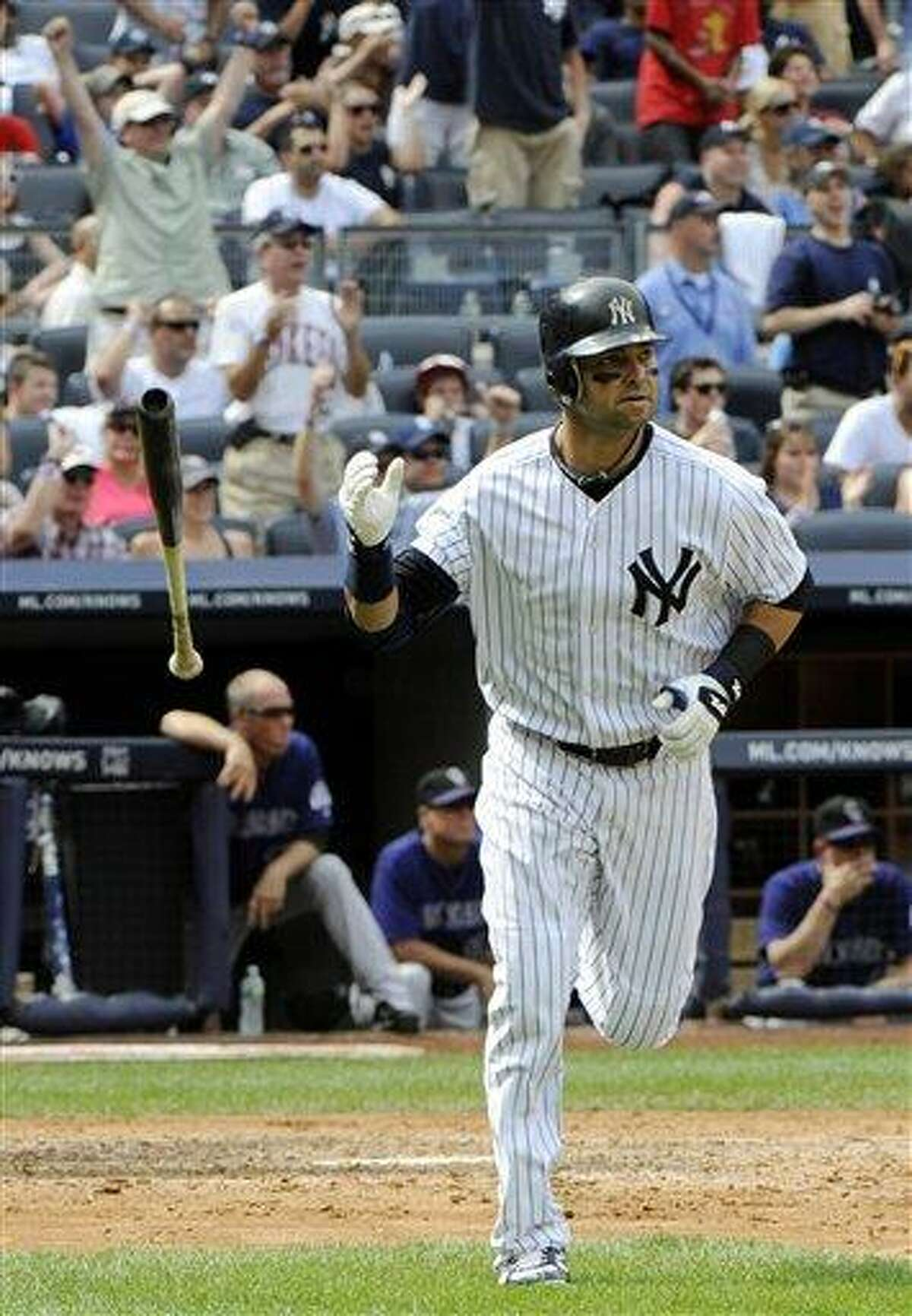 New York Yankees' Nick Swisher flips his bat after hitting a home run during the fifth inning of an interleague baseball game against the Colorado Rockies on Sunday, June 26, 2011, at Yankee Stadium in New York. (AP Photo/Bill Kostroun)