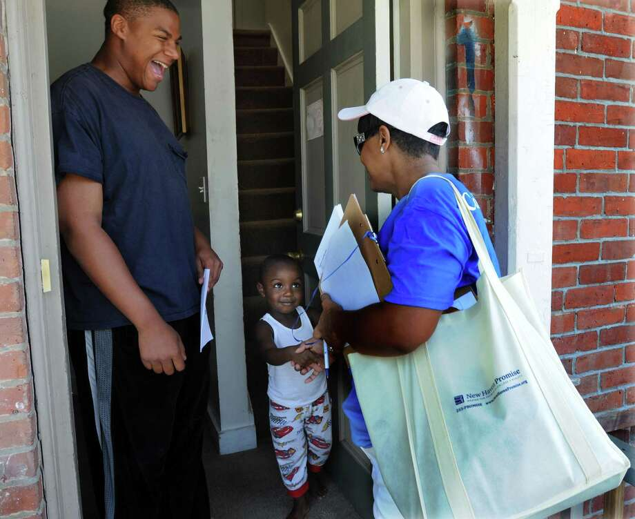 Volunteers for the New Haven Promise program, including Veronica Marion of New Haven, visited possible Promise students to hand out information to parents. Shamont Mabery at left is one of those students. His cousin Kevon Moore age 3 of New Haven meets Marion. Mara Lavitt/Register