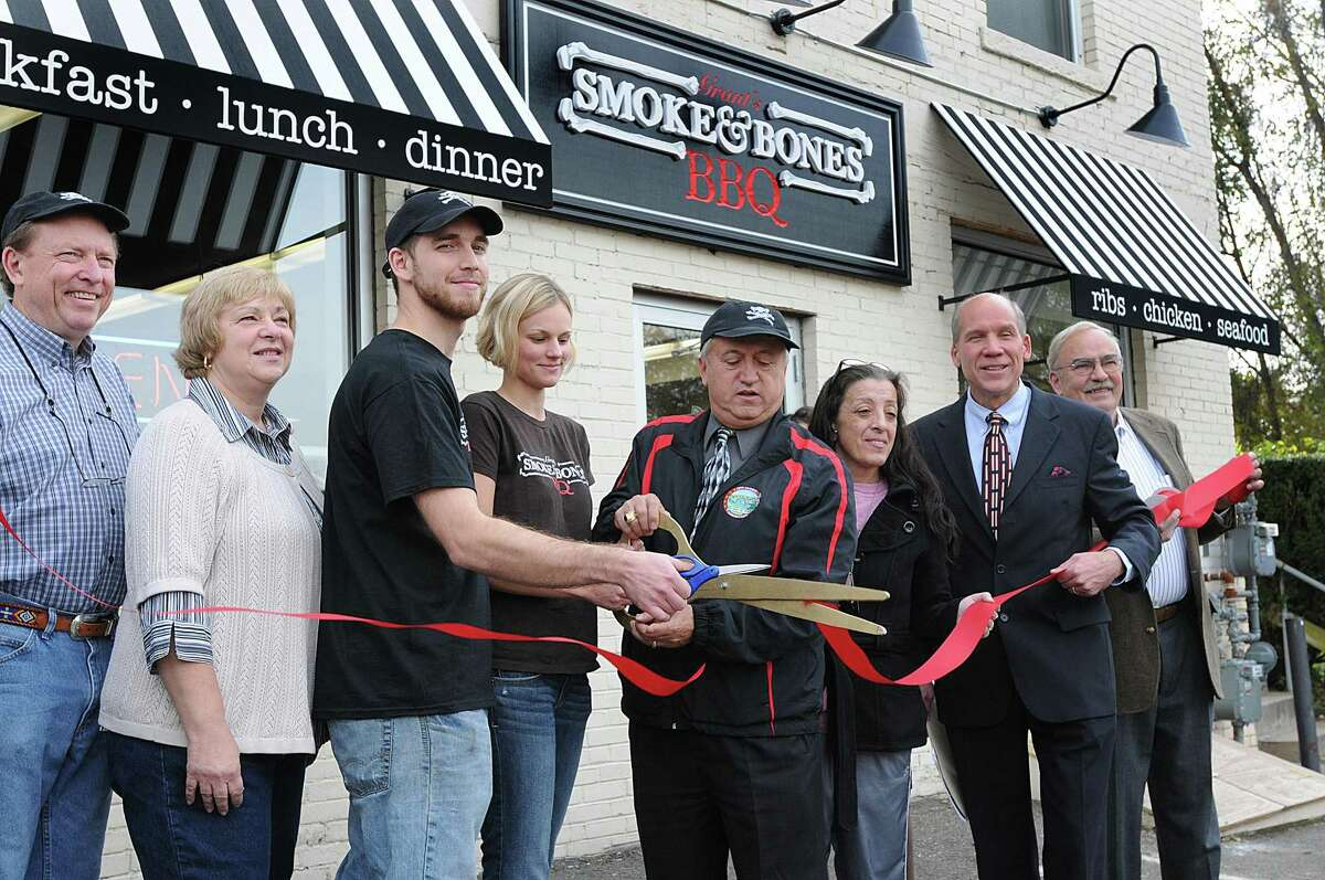 """Michael Grant, third from right, cuts the ribbon on his new restaurant, """"Smoke & Bones,"""" with family and dignitaries during the grand opening ceremony for the new barbecue eatery. They are, from left to right: David and Gail Grant, Sarah Grant, Derby Mayor Anthony Staffieri, Mary Porter, Bill Purcell and John O'Neill. (Peter Casolino/New Haven Register)"""