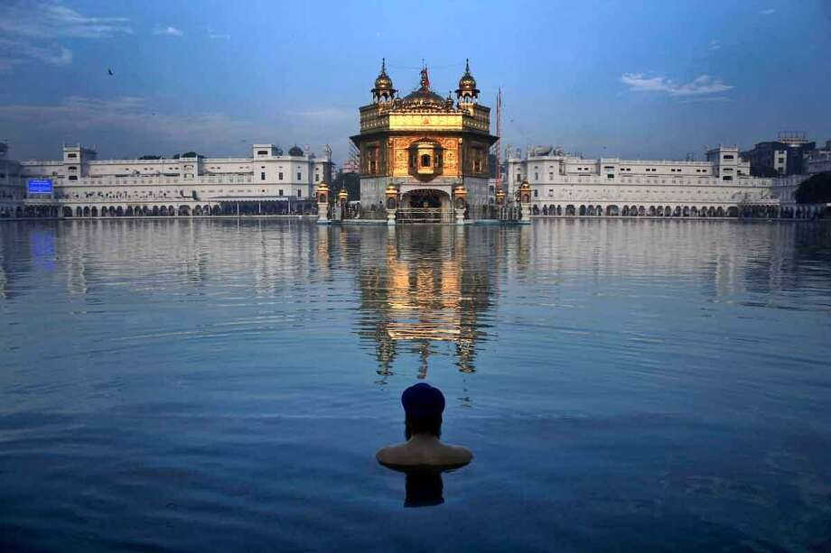 An Indian Sikh devotee takes a holy bath in the sacred pond of the Golden Temple, Sikhís holiest temple, during the birth anniversary of Guru Nanak, in Amritsar, India. AP Photo/Sanjeev Syal Photo: ASSOCIATED PRESS / The Associated Press2012